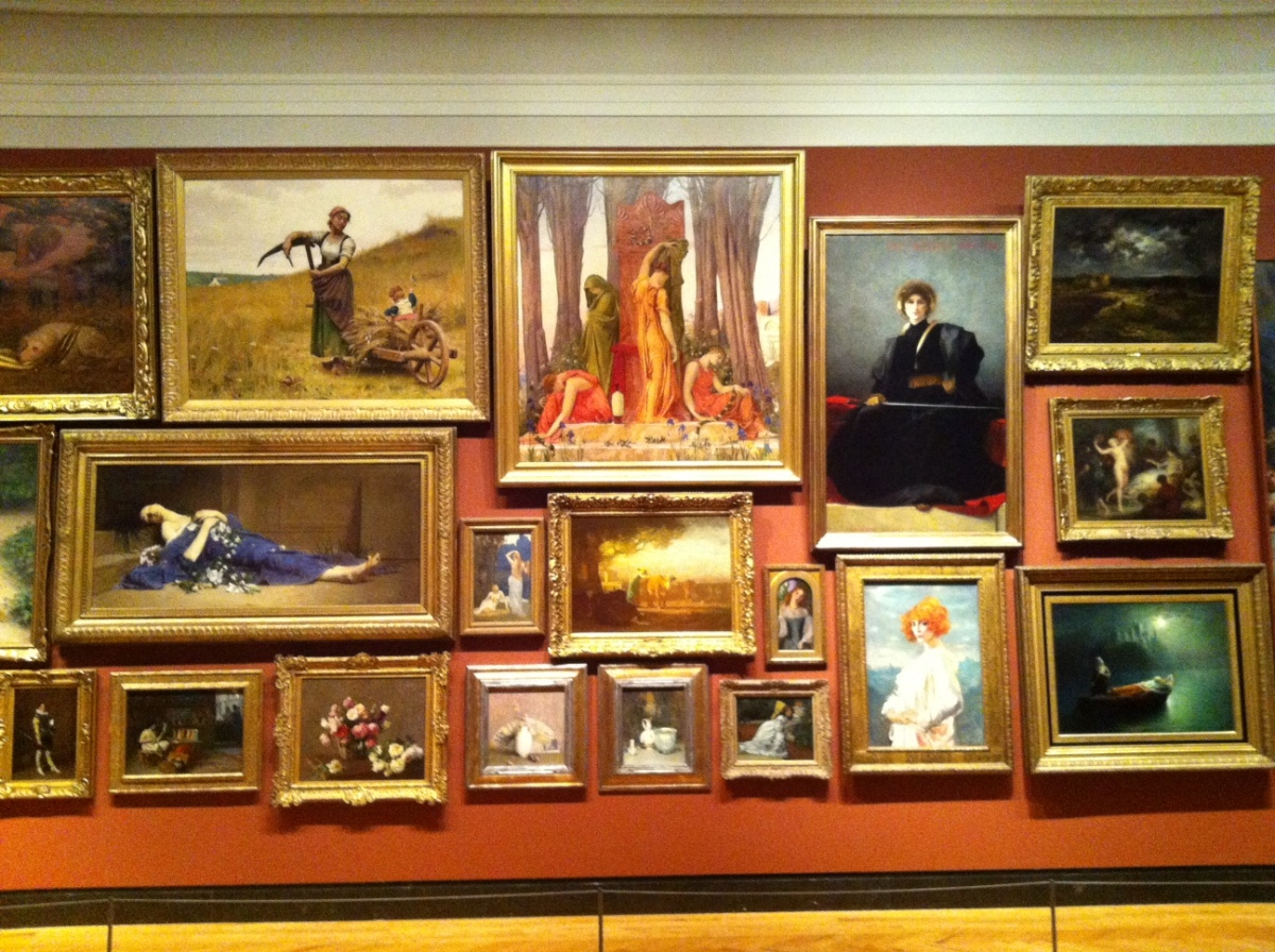 European paintings displayed in the style of a French salon (living room).